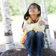 Little girl sitting under trees — Stock Photo