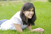 Beautiful teen girl lying on grass — Stock Photo