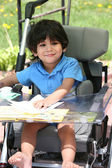 Disabled child in medical stroller — Stock Photo