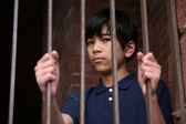 Boy standing behind bars — Stock Photo