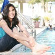 Young teen girl sitting by pool — Stock Photo