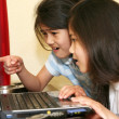 Two little girls working on a laptop - Stock Photo