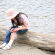 Girl with wound sitting on log — Stock Photo