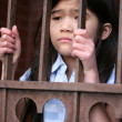 Little girl standing behind iron bars — Stock Photo #2658191