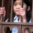 Little girl standing behind iron bars - Stock Photo