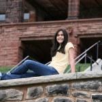 Teen girl sitting on rock ledge — Stock Photo