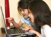 Two little girls working on a laptop — Foto de Stock