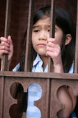 Little girl standing behind iron bars — Stock Photo