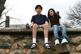 Two children sitting on rock ledge — Stock Photo