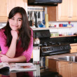 Teen girl relaxing in kitchen — Stock Photo