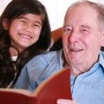 Elderly man and girl reading Bible — Stock Photo