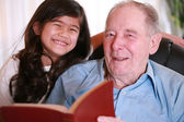 Elderly man and girl reading Bible — Foto de Stock