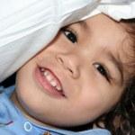 Little boy peeking under pillow — Stock Photo