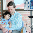 Foto Stock: Worried father holding child in Hospital