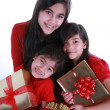 Three sisters holding presents — Stock Photo