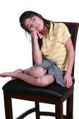 Sad girl sitting on chair — Stock Photo
