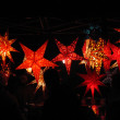 Glowing red christmas stars in the dark — Stock Photo