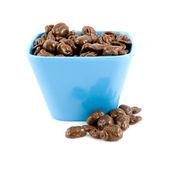 Blue bowl with chocolate raisins — Stock Photo
