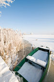 Green boat on ice in winter landscape — Stock Photo