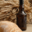 Freshly baked bread with stems of wheat and bottle of bear — 图库照片