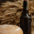 Stock Photo: Freshly baked bread with stems of wheat and bottle of bear