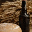 Freshly baked bread with stems of wheat and bottle of bear — Stock Photo #2393813