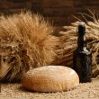 Freshly baked bread with stems of wheat and bottle of bear — Stock Photo