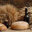 Freshly baked bread with stems of wheat and bottle of bear — Stock Photo #2393846