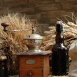 Stems of wheat with bottle of bear and coffee mill — Stok fotoğraf