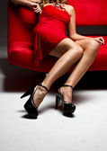 Girl sit on a red sofa — Stock Photo