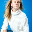 Young blond girl in white sweater — Stock Photo