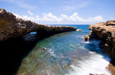 Rocky shore with natural bridge — Stockfoto