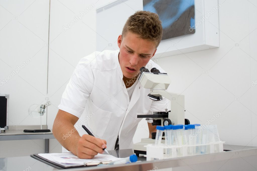 Young scientist or student looking through a microscope and writing down data — Stock Photo #2374536