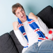 Crazy young man watching football — Stock Photo