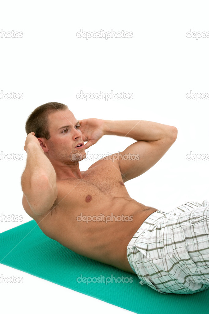 Young muscular man doing situp exercises on mat — Stock Photo #2458244