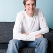 Young man sitting on the sofa — Stock Photo