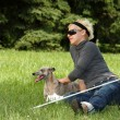 Blind woman with her litte dog - Stock Photo