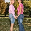 Sisters walking hand to hand — Stock Photo