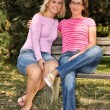 Sisters sitting on a bench — Stock Photo