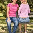 Happy sisters sitting on a bench — Stock Photo