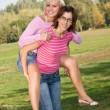 Girl piggybacking her sister in the park — Stock Photo