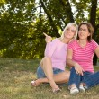 Two sisters sitting in the grass — Stock Photo #2456295