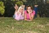 Twee zussen liggen in het gras — Stockfoto