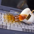 Coffee spilling on keyboard - Stock Photo