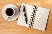 Blocco note spirale vuota, tazza di caffè e — Foto Stock