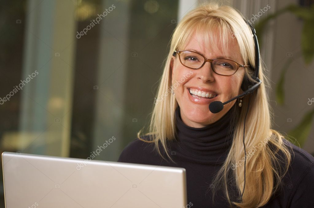 Attractive businesswoman smiles as she talks on her phone headset. — Stock Photo #2284319