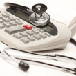 Black Stethoscope on a Calculator - Stock Photo