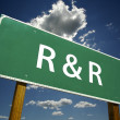 R and R Road Sign with dramatic clouds and sky. — Stock Photo