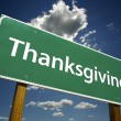Stock Photo: Thanksgiving Green Road Sign Against Sky