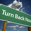 Turn Back Now Green Road Sign — Stock Photo
